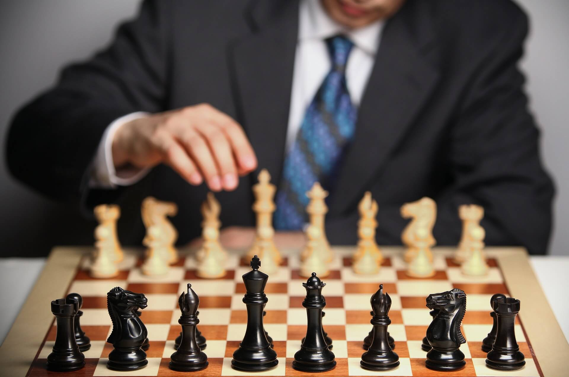 POV image of business man playing chess with black pieces facing viewer